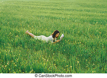 Girl lying on summer meadow and reading a book