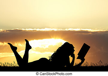 girl lying on the grass reads a book at sunset