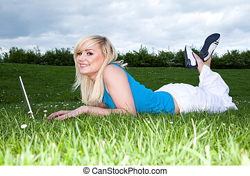 Girl lying on the grass working on a laptop