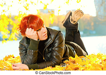 girl lying on yellow autumn leaves