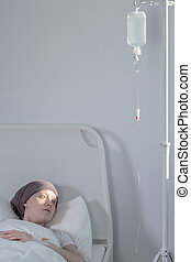 Girl lying under drip - Young girl with cancer lying in ...