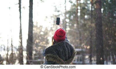 girl make a selfi in winter in sunset