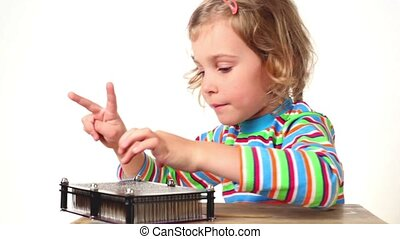 Girl make imprint of two fingers up on pin board of imprint toy