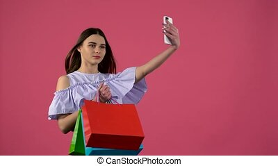 Girl make selfies with colorful packages. Pink background -...