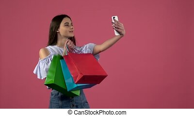 Girl make selfies with colorful packages. Pink background....