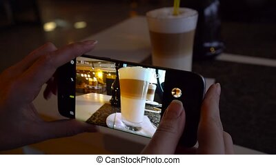 Girl makes a photo of a latte on a smartphone in a cafe...