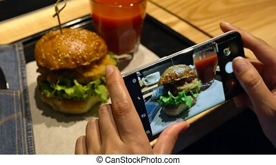 Girl makes a photo of burger and tomato juice on a...