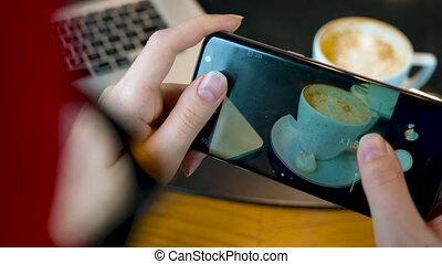 Girl makes a photo of coffee on a smartphone in a cafe close up