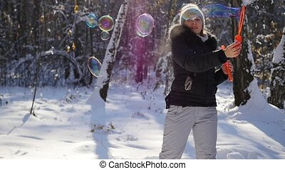 girl makes big soap bubbles with delight in winter Park on a Sunny day