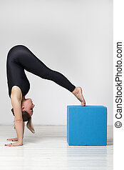Girl makes complicated inverted asana, doing yoga