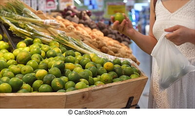 Girl makes purchases in a supermarket, healthy food, lime in the market, supermarket. Concept of buying products. Choosing food in the supermarket for cooking.