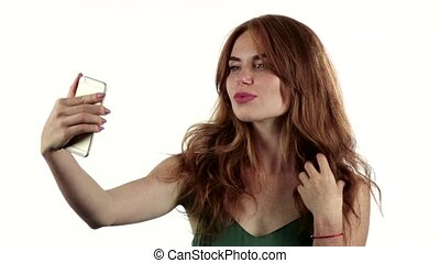 Girl makes selfie on her smartphone. White background. Slow motion