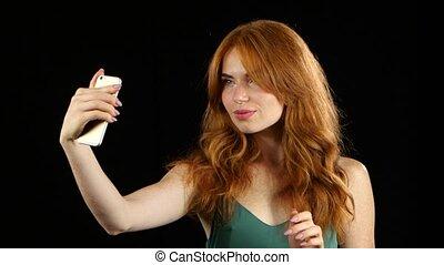 Girl makes selfie on her smartphone. Black background - Red...