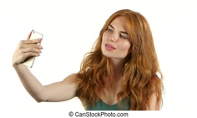 Girl makes selfie on her smartphone. White background