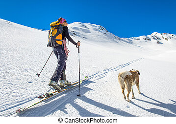 Girl makes ski mountaineering with dog.
