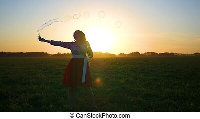 girl makes soap bubbles at sunset