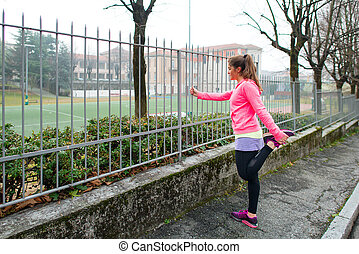 Girl makes stretching in city