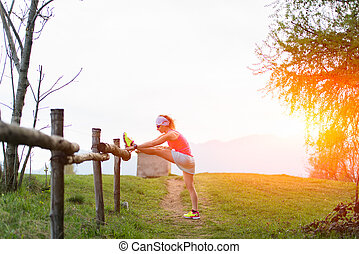 Girl makes stretching in the nature of a fence