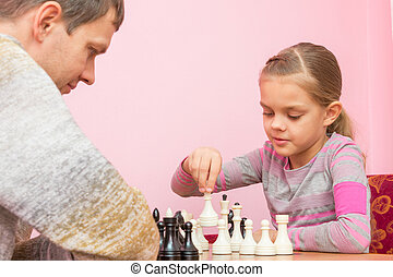 Girl makes the next move while playing chess with the coach