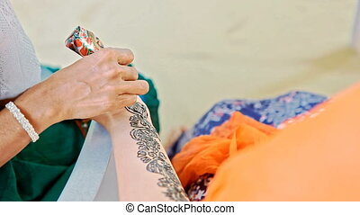 Girl Makes Traditional Painting with Henna on Bride Hand