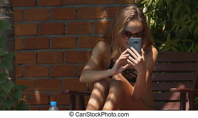 Girl Makes Video Using Phone Sitting under Canopy - closeup...