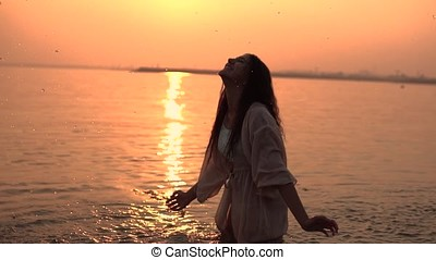 Girl making beautiful splashes in the river against the background of the sun