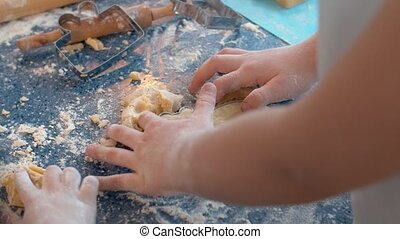 Close up hands of a girl making cookies with a cookie cutter. Children cooking pastry in bright kitchen. Home bakery concept