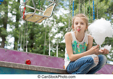 Girl making faces while eating cotton candy