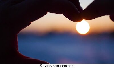 girl making heart with hands in the sun. Silhouette hand in heart shape with inside the sunset. Winter