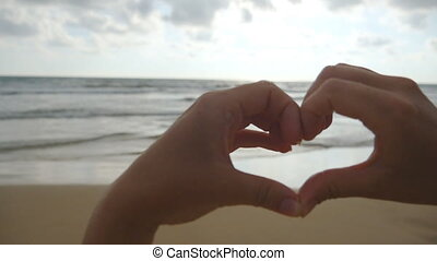 Girl making heart with her hands over sea background with...
