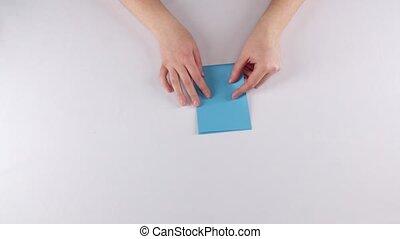 Girl making origami. Envelope. Time lapse