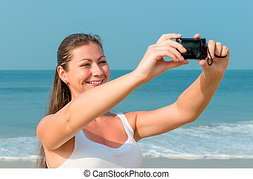 girl making self photo on a background of the sea