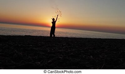 girl manages fire near the sea at sunset
