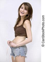 girl measuring her waist - woman measuring her waist wearing...