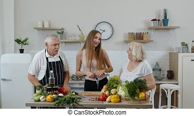 Girl measuring with tape measure her slim waist and braging in front of grandparents. Raw food diet