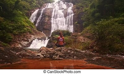 Girl Meditates in Yoga Pose by Lake against Water Cascade