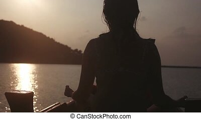 Girl meditates sits in pose of lotos on boat in the sea...