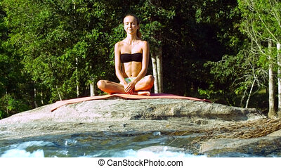 girl meditates with closed eyes in pose Half Lotus by river