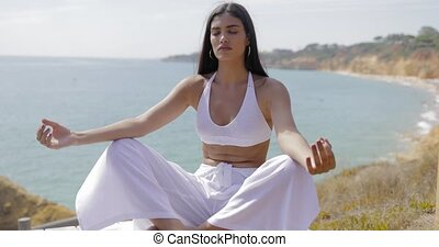 Girl meditating on shoreline - Young ethnic model in white...