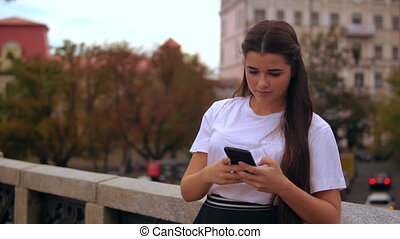 girl messaging on mobile outdoors