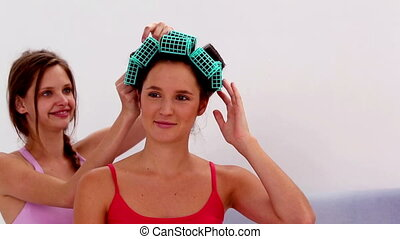 Girl messing up friends hair rollers at girls night in at...