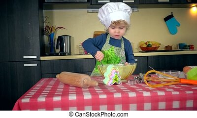 girl mix flour in bowl on table in kitchen. Girl in apron and white chef hat. 4K