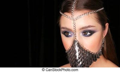 Girl model in unusual iron stylish muzzle. Symbol of the...