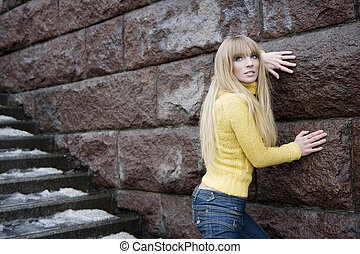 Girl model next to a stone wall and stairs