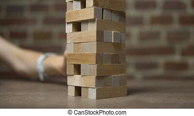 Girl Moves Brick out in Jenga Game - Jenga game, caucasian...