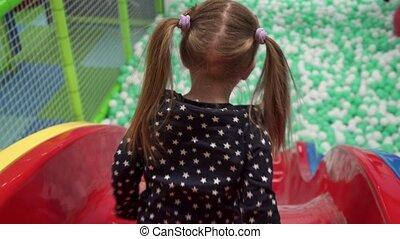 Girl moving down slide on playground in children's center