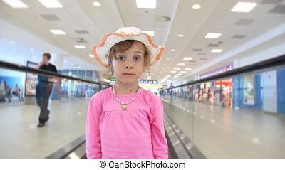 Girl moving on speedwalk at airport - Girl in pink suit and...