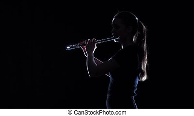 Girl musician blows the motif in wind instrument. Slow motion
