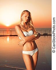 Girl near pool on the sunrise