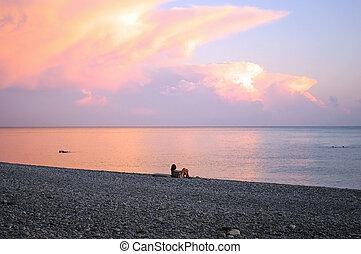 Girl near the sea at sunset